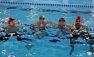 Aileleriyle birlikte yüzerek engelleri aşıyorlar